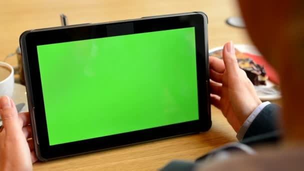 La donna lavora sullo schermo del Tablet PC verde in caffè - caffè e torta