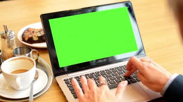 Donna di affari che funziona sullo schermo di computer verde (notebook) nel caffè - caffè e torta