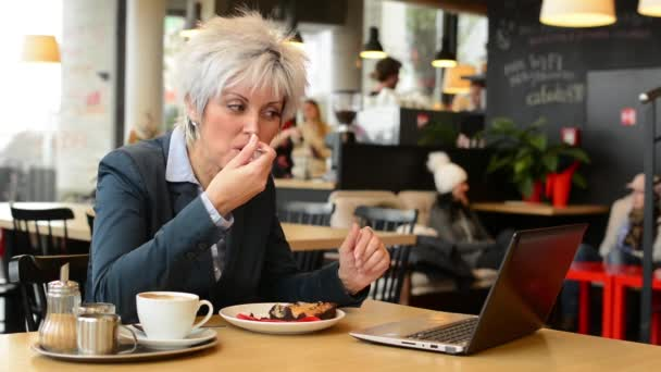 Middle aged woman eats cake in cafe - notebook (computer)