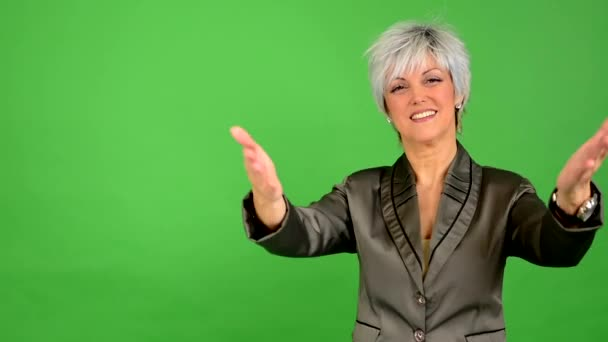 Business middle aged woman welcomes - green screen - studio