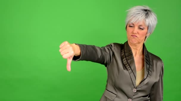 Business middle aged woman shows thumb on disagreement - green screen - studio