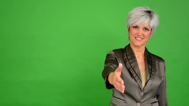 Business middle aged woman gives a hand in greeting and smiles - green screen - studio
