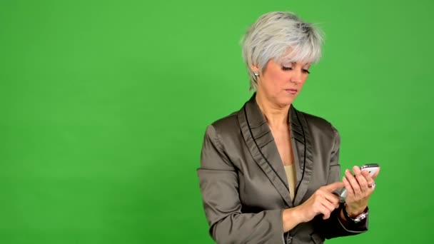 Business middle aged woman works on smartphone - green screen - studio