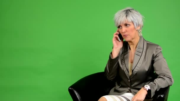 Business middle aged woman sits and phone and smiles - green screen - studio