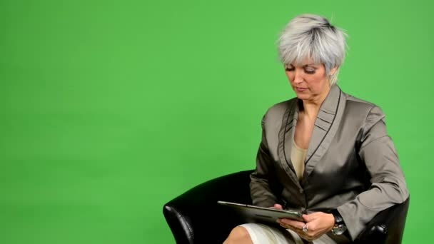 Obchodní středního věku žena sedí a pracuje na tabletu - fabion - studio