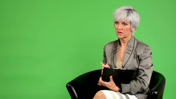 Business middle aged woman sits and writes to paper and smiles - green screen - studio