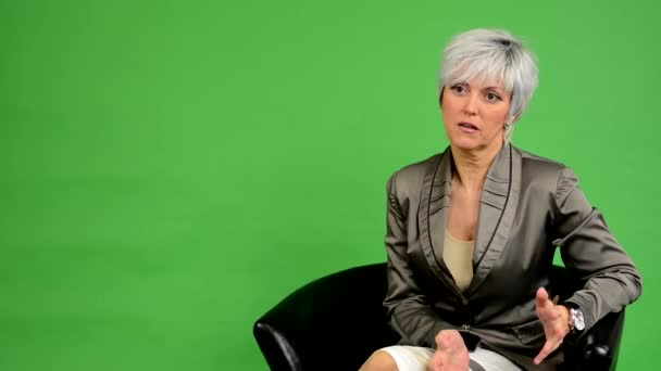 Business middle aged woman sits and talks (interview) - green screen - studio