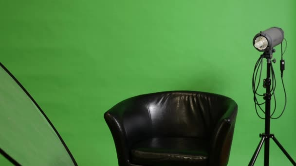 Studio with chair and photographic equipment (light and reflecting plate) - switch on lights - green screen