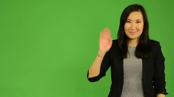 Young attractive asian woman waves with hand - green screen studio