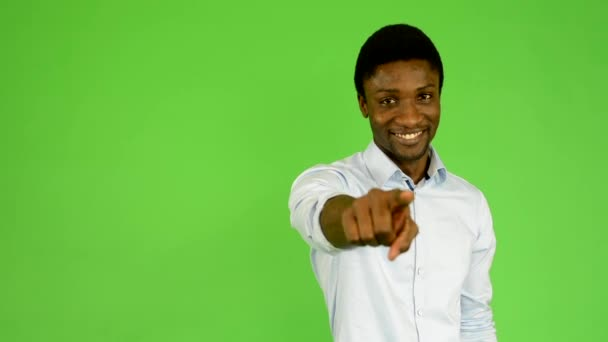 Young handsome black man points to camera - green screen - studio