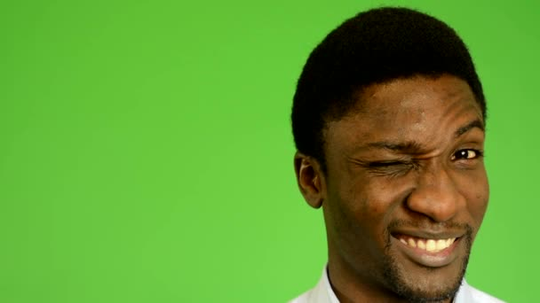 Young handsome black man winks the eye- green screen - studio - closeup