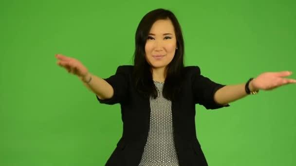 junge attraktive asiatische Frau begrüßt - Green Screen Studio