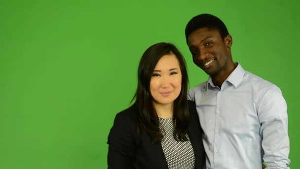 Happy couple kiss and smile to camera - black man and asian woman - green screen studio