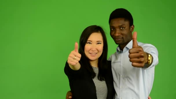 Happy couple show thumb on agreement - black man and asian woman - green screen studio