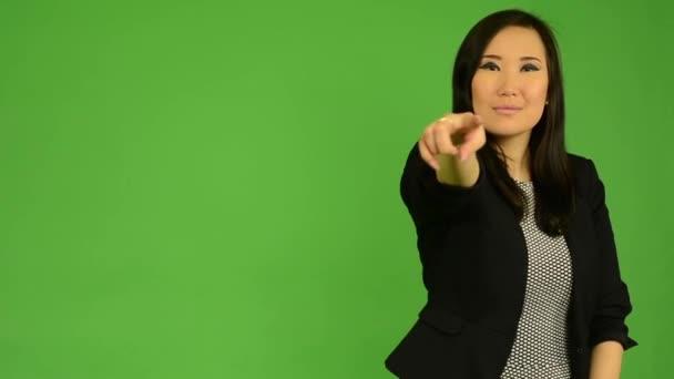 Mladá atraktivní asijské žena ukazuje na kameru - zelené obrazovky studio