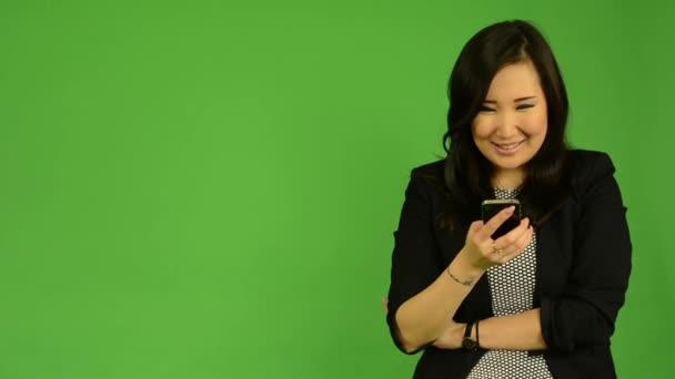junge attraktive Asiatin arbeitet am Smartphone und lächelt - Green Screen Studio
