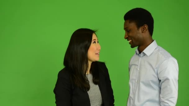Happy couple talk (conversation) - black man and asian woman - green screen studio