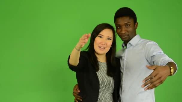 Happy couple invite and smile - black man and asian woman - green screen studio