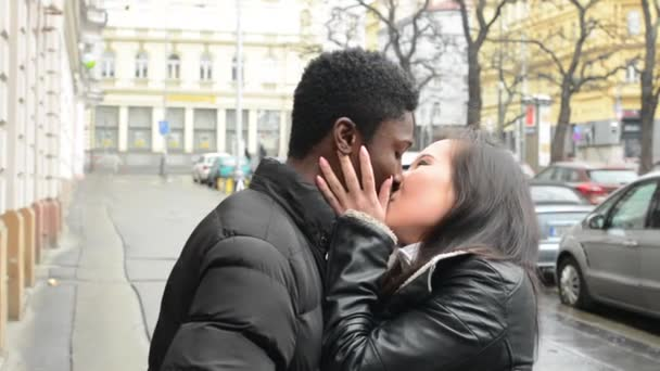 Young model happy couple in love (black man and asian woman) - couple kiss - urban street with cars - city