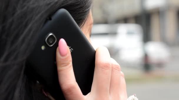 Mladá atraktivní žena telefon v městě - městské ulice s automobily - záběr na mobil