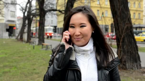 junge attraktive asiatische Frau telefoniert und lächelt - Stadtstraße mit Autos - Stadt