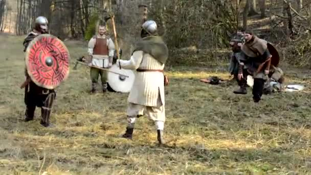 Medieval battle - war - soldiers fight - two men fight and other soldiers watch them