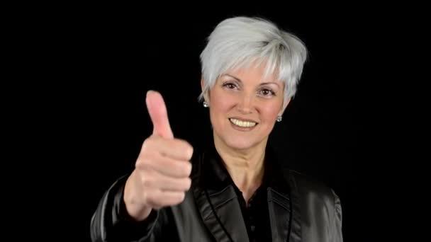 Obchodní žena středního věku ukazuje palec na dohodu - černé pozadí - studio - detail