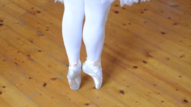 Young ballerina dancing on the parquet block (hall) - closeup foot