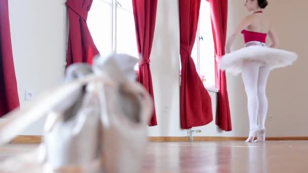 Young ballerina dancing - ballet shoes - interior - red curtain
