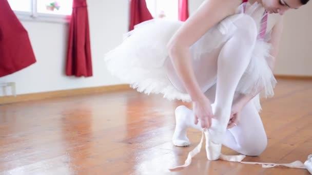 junge Ballerina zieht Ballettschuhe und Ballerinas an