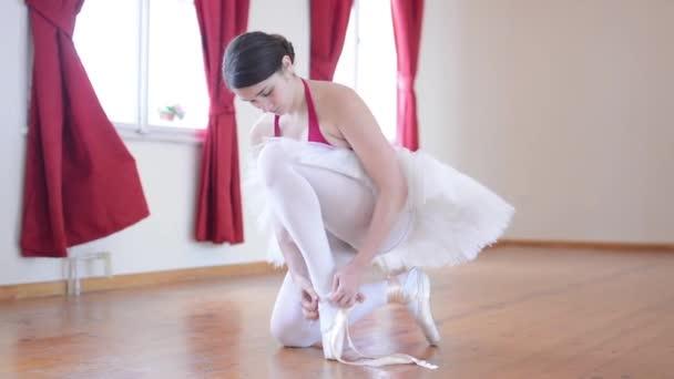junge Ballerina bereitet sich auf den Tanz vor - Ballerina bindet Schuhe