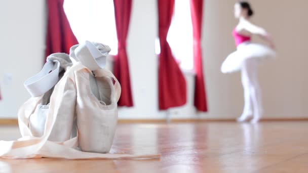 Detail ballet shoes - ballerina dancing in the background - interior - red curtain