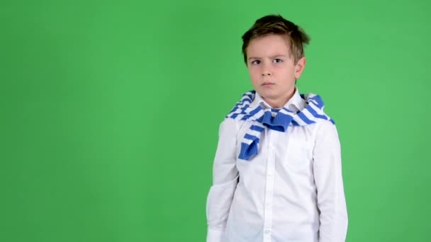 Young handsome child boy thumb on rejection - green screen - studio