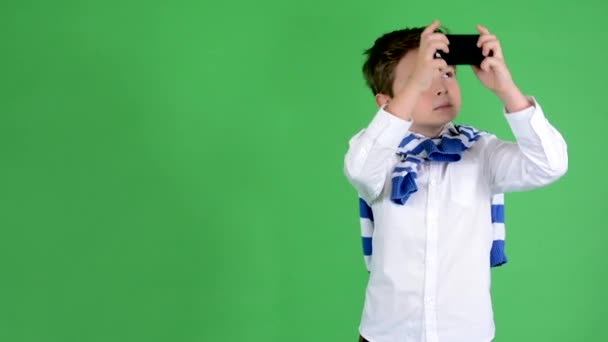 young handsome child boy photographs with smartphone green screen