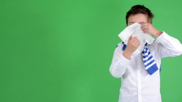 kleiner gutaussehender Junge bläst seine Nase in ein Taschentuch - grüner Bildschirm - Studio