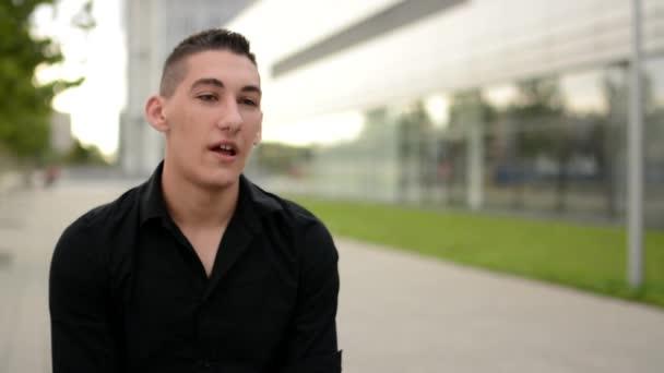 Mladý pohledný muž mluví do kamery (rozhovor) - ulice ve městě - detail