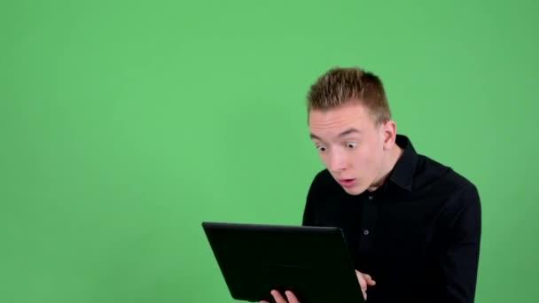 Mladý pohledný muž pracuje na počítač (laptop) a raduje se - zelené obrazovky - studio