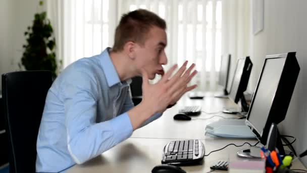 junger schöner Mann arbeitet am Desktop-Computer und ist wütend