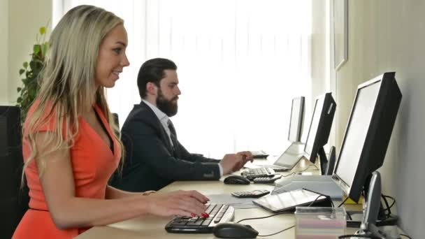 woman and man work on desktop computer and rejoice in the office (workers)