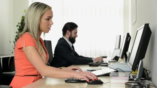 young attractive woman and handsome man work on the desktop computer in office and smiles to camera