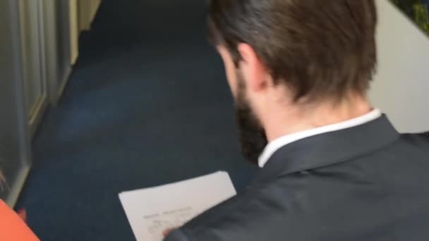 business man and woman walking in the office and talking together about documents - steadicam - shot over shoulder