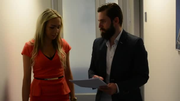 business man and woman walking in the office and talking together about documents - steadicam