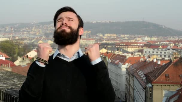 young handsome man with full-beard (hipster) is depressed - city in background
