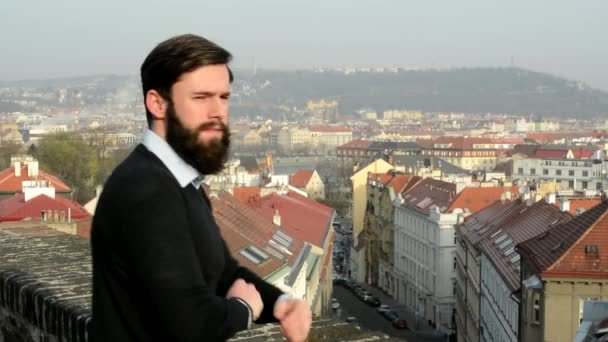 young handsome man with full-beard (hipster) smiles to camera (fold arms) - city in background