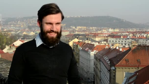 young handsome man with full-beard (hipster) shows thumb on agreement - city in background