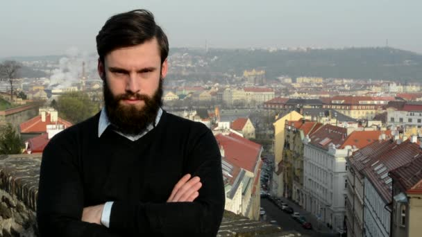young handsome man with full-beard (hipster) looks to camera (confident look) - city in background