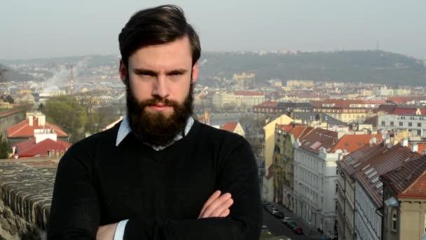 mladý pohledný muž s plnovousem (hipster) vypadá na kameru (sebevědomý vzhled) - město v pozadí