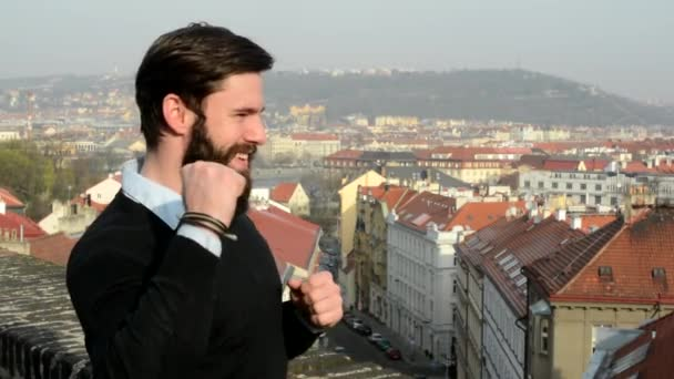 young handsome man with full-beard (hipster) rejoices - city in background
