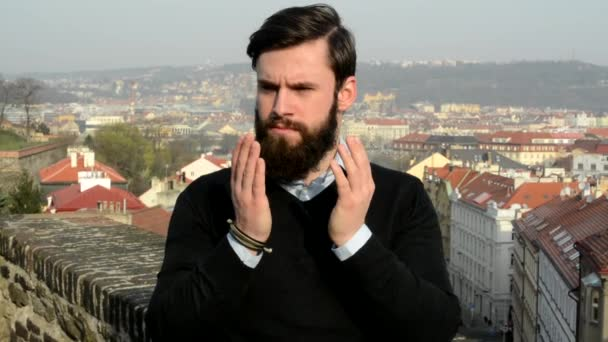 young handsome man with full-beard (hipster) covers his face with arms and then he is suprised - city in background