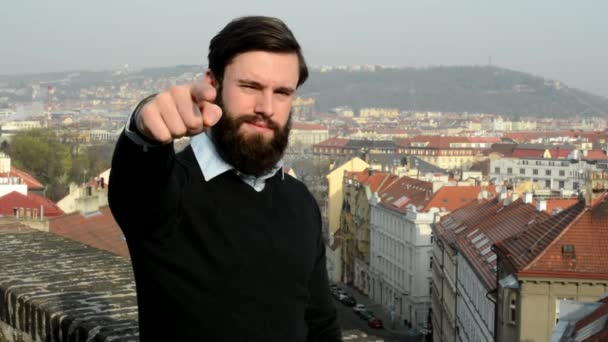 young handsome man with full-beard (hipster) points to camera - city in background